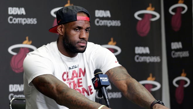 Miami Heat's LeBron James pauses during a news conference in Miami, Tuesday, June 17, 2014. James says he's going on vacation with his family before making any decisions about his future. The Miami Heat held their season-wrapup team meeting on Tuesday afternoon and one of the biggest questions is about the future of the roster. James could become a free agent in a couple of weeks and the four-time MVP says he still has not thought about his plans.