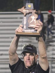 Groves head coach Brendan Flaherty proudly holds up