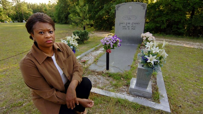 On June 8, 2005,  Angela Lewis pauses at the gravesite of her father, James Chaney, who was murdered in 1964 for his role in Freedom Summer, an initiative to register black voters. Because of continued gravesite desecration, Chaney's headstone now is supported by metal beams.