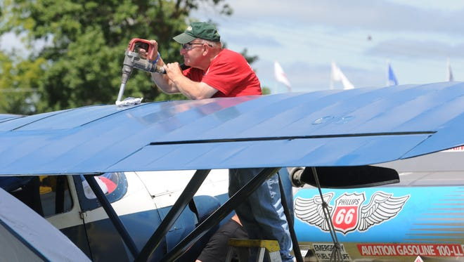 Mike Albashian with Basler Flight Service puts Av gas into a 1939 Fairchild.  Experimental Aircraft Associations AirVenture kicked off on July, 29. 2013.  People from all over the world travel to Oshkosh for AirVenture making Oshkosh one of the busiest airports in the world.