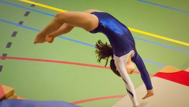 Young gymnast girl performing jump back handspring while practicing for the competition