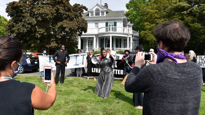 Esther Ngotho, of Beverly Human Rights Committee, addresses protestors outside the home of Governor Charlie Baker in Swampscott during a Black Lives Matter rolling rally protest on Wednesday, June 3, 2020.