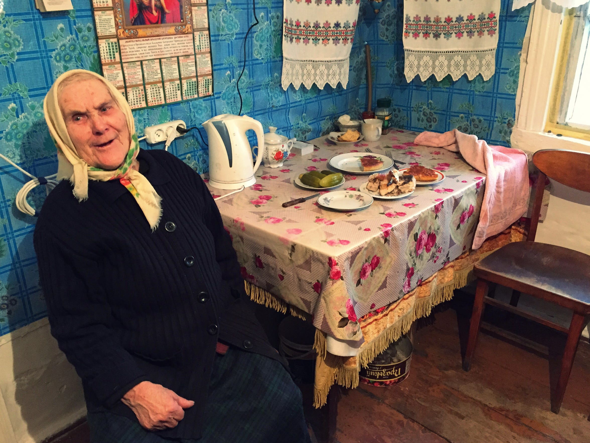 Ganay Zavorotnya sits next to a table insider her home in the Chernobyl Exclusion Zone on March 1, 2016.