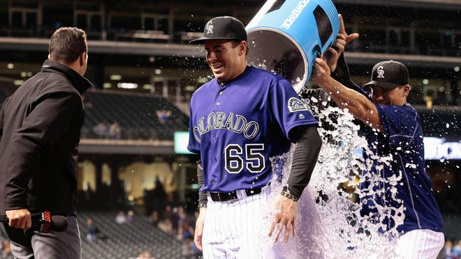 Former FSU All-American shortstop and Colorado Rockies right fielder Stephen Cardullo is doused with water by teammates after a game against the Los Angeles Dodgers at Coors Field last month.