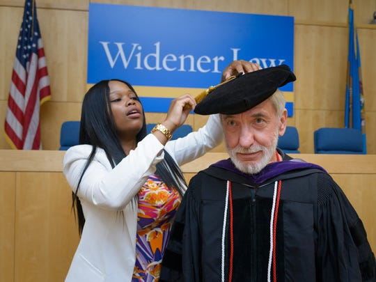 Jocelyn Pugh of New Castle, left, helps Robert Gorkin, a 70-year-old graduate that already has a Ph.D. in biology as well as a medical degree, with his cap and gown Saturday. Gorkin added a Widener law degree to his list of educational accomplishments.
