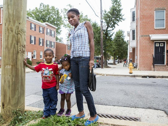 Ja-mé Meadows poses for a portrait with her children, four year-old Jonathan Howard (left) and three year-old Carolina Howard (center) in Wilmington's West Center City neighborhood on Tuesday afternoon. Meadows said the children are not allowed to play outside without her because of gun violence.
