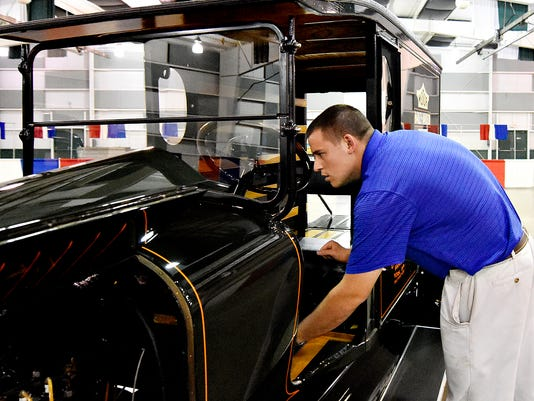 York Fair Sales Manager Cody Cashman looks over a 1917 Pullman, which was one of the last manufactured in York, and will be on display as part of the 'York Fair through the Years' exhibit in Memorial Hall on the York Fair Grounds in York, Pa. on Friday, Sept. 4, 2015. Dawn J. Sagert - dsagert@yorkdispatch.com