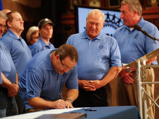 UAW President Dennis Williams, center, watches as Volkswagen employee Jonathan Walden signs the UAW charter at a news conference in July 2015 to announce a new UAW union in Chattanooga for VW workers.