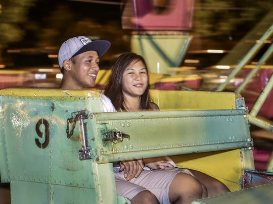 Gavin Salas of Agana Heights and Camilla Quenga of Barrigada blur by sharing smiles on the Scrambler ride at the Liberation Carnival in Tiyan on June 13.