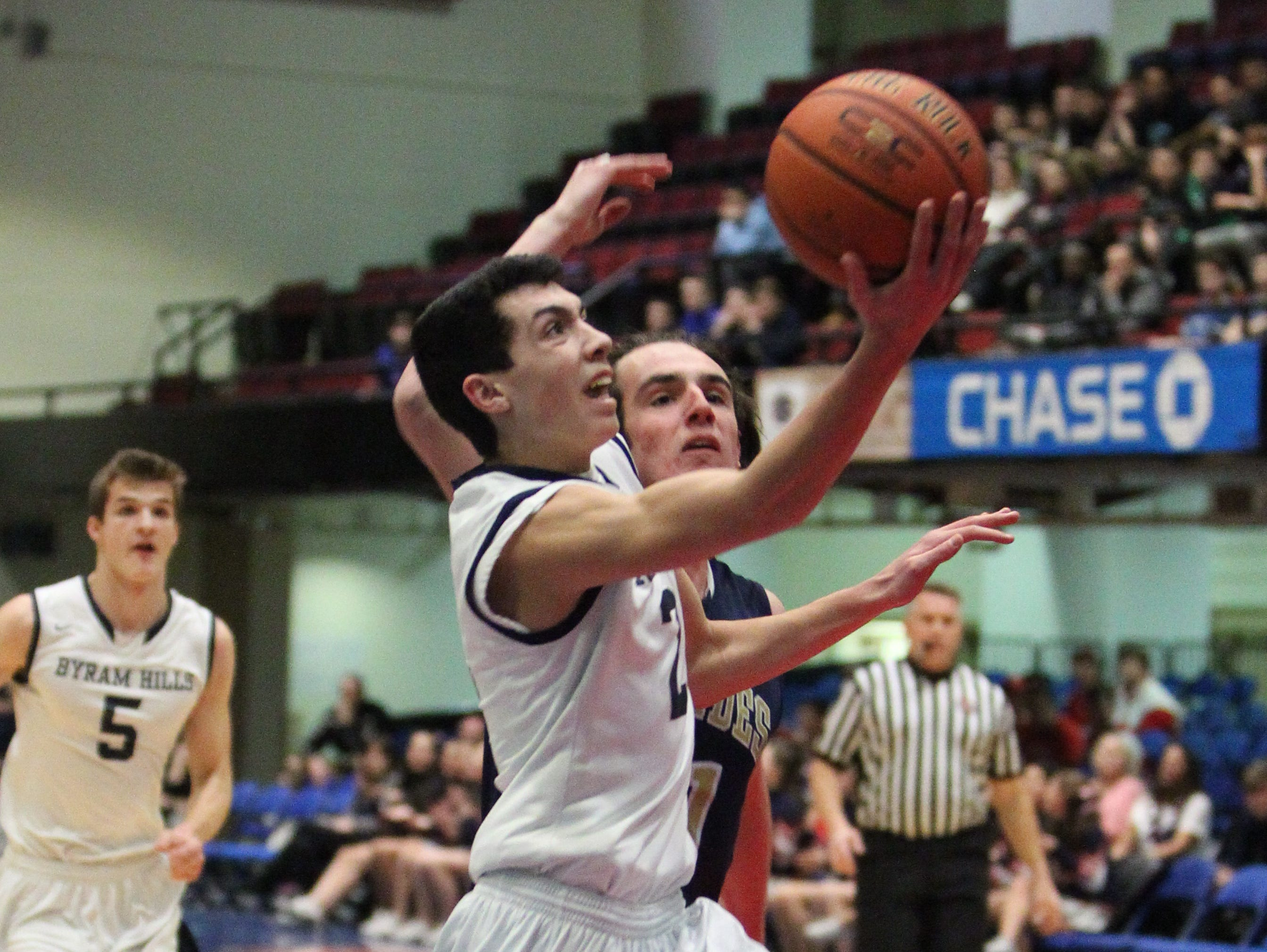 Byram Hills' Skylar Sinon drives past Lourdes' Jeremy Waters during their Section 1 Class A semifinal at the Westchester County Center Feb. 22, 2016.