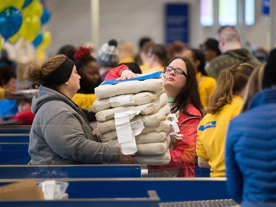 December 14, 2016 - Shoppers carry a stack of cushions through checkout during the grand opening of the new Memphis Ikea store.
