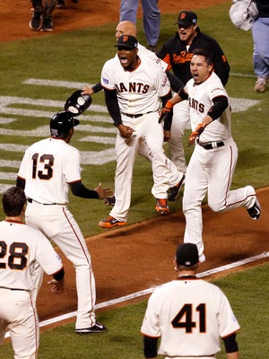 Oct 16, 2014; San Francisco, CA, USA; San Francisco Giants left fielder Travis Ishikawa (45) celebrates with teammates after hitting a walk off three run home run against the St. Louis Cardinals during the ninth inning of game five of the 2014 NLCS playoff at AT&T Park.Mandatory Credit: Kelley L Cox-USA TODAY Sports