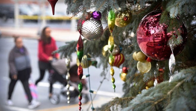 Pedestrians pass by the 23-foot blue spruce Christmas tree at North Ninth and Cumberland streets in Lebanon on Wednesday. The National Fire Protection Association recommends that Christmas trees be recycled when they lose their function. The Greater Lebanon Refuse Authority at 1610 Russell Road in North Lebanon Township will recycle your tree for free.