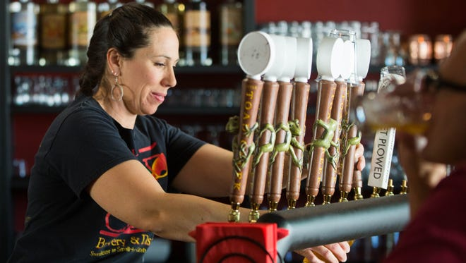 Carol Ayon, a bartender at Little Toad Creek Brewery and Distillery in Las Cruces, pours a beer for a customer on Friday May 18.