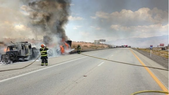 Firefighters try to control the semi fire on I-15 Sunday.