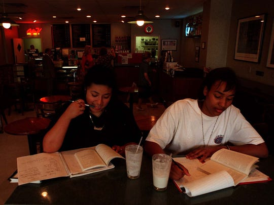 Esmeralda Perez, left, and Kamahra Ewing do homework and enjoy Caffe Venezia in East Lansing, July 18, 1996.