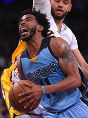 Grizzlies guard Mike Conley (11) gets past Lakers guard Tyler Ennis (11) as he drives to the basket in the first half Sunday.