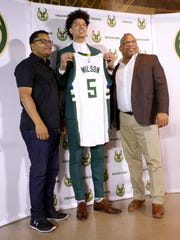D.J. Wilson holds up his jersey with two of his former coaches from a high school travel team, Lehron Dodson (left) and Vonn Webb (right). The Milwaukee Bucks' first-round NBA draft pick was introduced to the media at a news conference Monday, June 26, 2017.