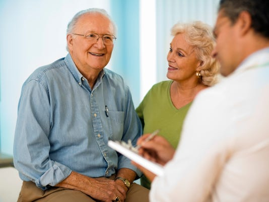 Senior couple talking with doctor.