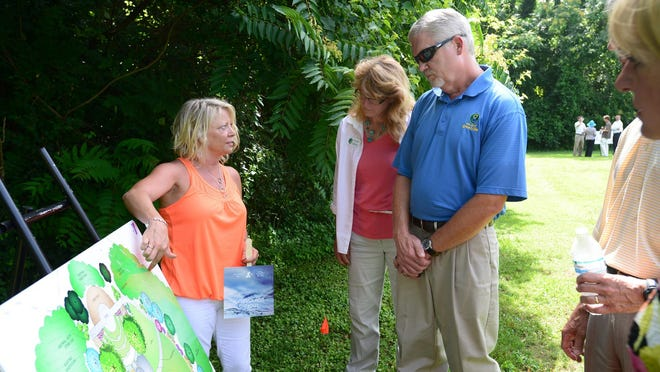 People attend a press conference outside of the Caine Halter Family YMCA on Tuesday, where building plans for new amphitheater and gardens along the Reedy River were unveiled.