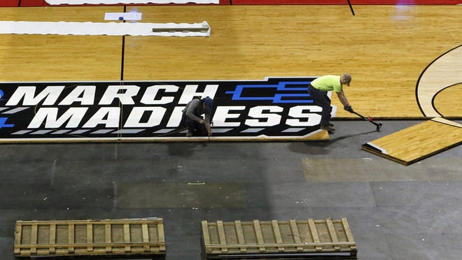 Students from OSU who usually lay down the floor at Value City Arena work at installing a floor  March 17, 2019 at Nationwide Arena. The floor brought in for the NCAA Men's Basketball Championship First and Second Rounds consists of 217 maple wood panels.