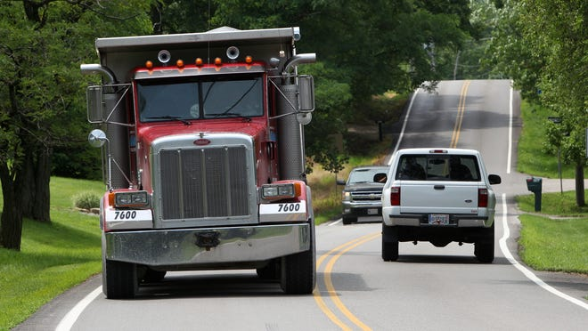 A dump truck passes a pickup truck near the 1400 block of Mt. Zion Road (Ky. 536) in an area between I-75 and U.S. 42 the state is buying up right of way to widen the highway into four lanes.