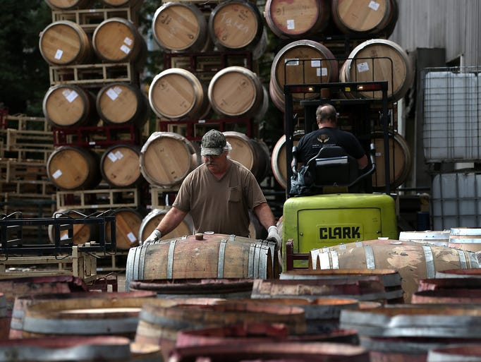 Workers stack broken wine barrels after a massive collapse at a wine-barrel storage facility.