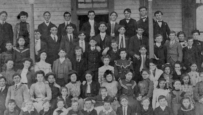 """Professor T.M. Clark and his wife Alice (lower right) with the 1901 class at Bay View College in Portland. Younger children attended the college as day students, their tuition paid by the Portland school system. The school day started with a prayer and Bible teaching. Prof. Clark emphasized the school was not affiliated with any religion though all the teachers were """"earnest Christians."""""""