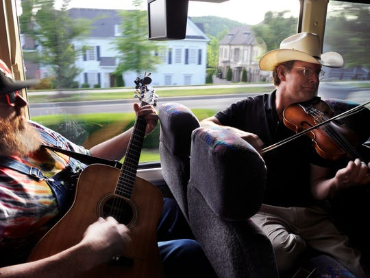 Travis Stinson, left, and Johnny Campbell of the band the Bluegrass Drifters perform on a bus from Nashville to the Music City Roots in Franklin.