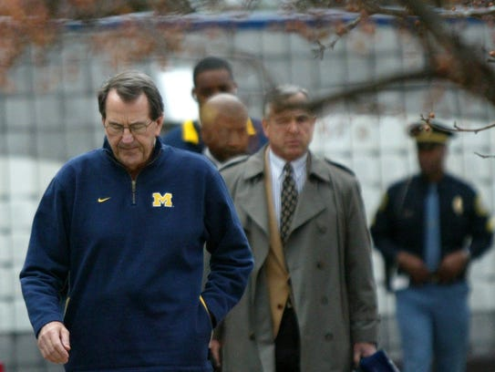 U-M coach Lloyd Carr is the last to walk to the bus