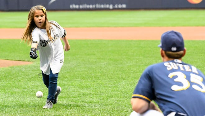 Hailey Dawson, age 8, throws the ceremonial first pitch to former Moeller High School standout and Milwaukee Brewers pitcher Brent Suter (35) before a game against the Chicago Cubs at Miller Park. By using a robotic hand made with a 3-D printer, Dawson hopes to throw the ceremonial first pitch in every MLB ballpark.