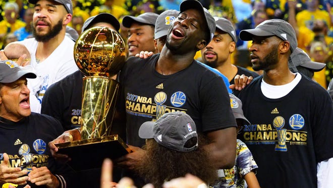 Golden State Warriors forward Draymond Green (23) celebrates with the Larry O'Brien Trophy after beating the Cleveland Cavaliers in game five of the 2017 NBA Finals at Oracle Arena.