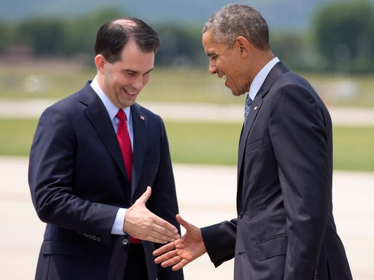 President Barack Obama, right, is greeted by Wisconsin