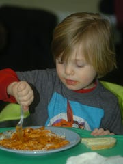 Owen Spilker, 3, from Royal Oak, stabs at some mostaccioli during the St. Patrick's Day Parade fundraiser at the VFW in Royal Oak.