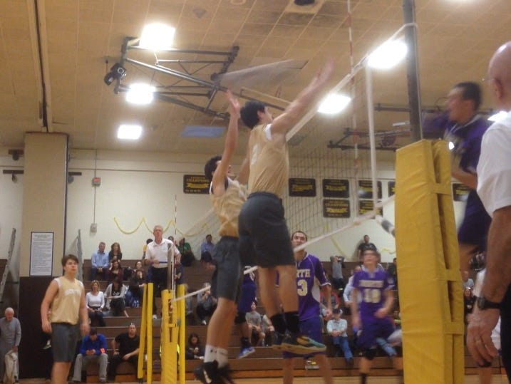 Clarkstown North's Jordan Housman gets a kill past two Clarkstown South defenders in the Section 1 boys volleyball final at Clarkstown South High School. Oct. 29, 2015.