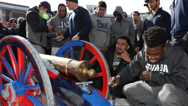 Nevada running back James Butler, right, helps teammates paint the Fremont Cannon blue in front of the Joe Crowley Student Union on Sunday.