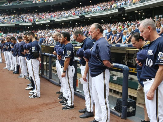 Milwaukee Brewers Manager Ron Roenicke (10) at his team observes a moment of silence before their baseball game against the St. Louis Cardinals. Saturday, July 12, 2014, in Milwaukee. Brewers shortstop Jean Segura's nine month old son passed away Friday in the Domincan Republic. (AP Photo/Jeffrey Phelps)
