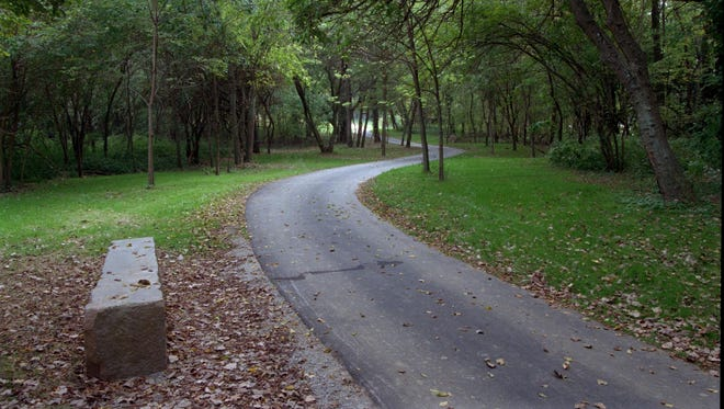 This limestone bench offers hikers a resting spot along the Riverwalk as it curves through Shawnee Park.
