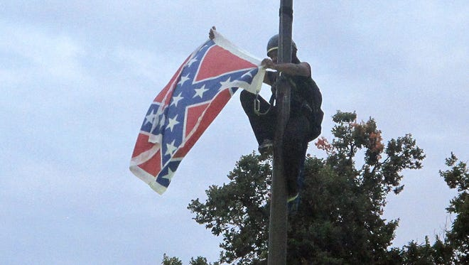 Bree Newsome of Charlotte, N.C., removes the Confederate battle flag at a Confederate monument at the Statehouse in Columbia, S.C., on Saturday, June, 27, 2015. She was taken into custody when she came down. The flag was raised again by capitol workers about 45 minutes later.  (AP Photo/Bruce Smith) ORG XMIT: SCBS103