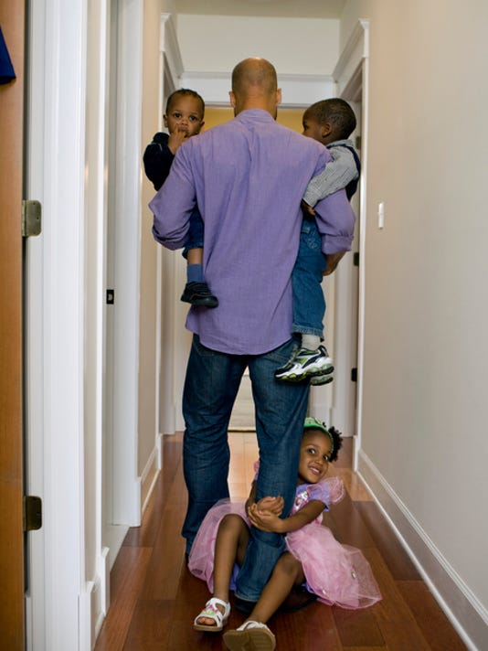 Father walking down hall with kids
