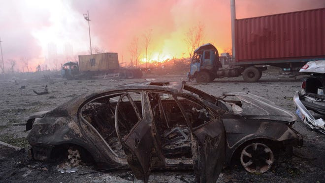 This photo taken on August 13, 2015, shows a destroyed car as a fire continues to burn after a series of explosions at a chemical warehouse hit the city of Tianjin, in northern China.