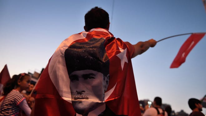 A boy is wrapped in a flag of the founder of modern Turkey Mustafa Kemal Ataturk on Taksim square in Istanbul on July 17.