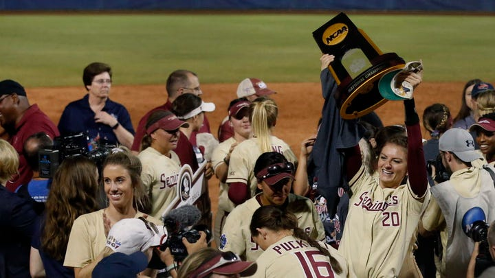 Florida State's Kylee Hanson holds the trophy as players celebrate after defeating Washington to win the national title.