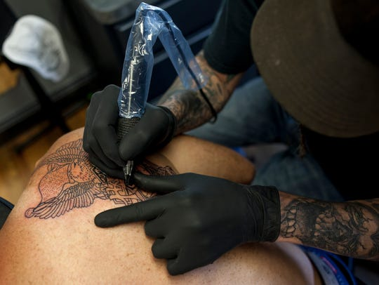 Jon Reno works on a tattoo with Michael Spangler, of