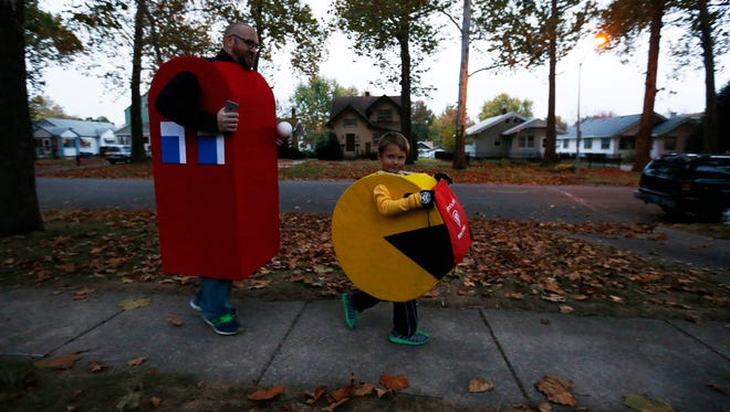 "Rob Fox (left) and Calvin Waggoner, 6, walk from house to house in their Pac-Man costumes Friday, Oct. 30, 2015, during Beggars' Night in Des Moines. Fox said he and Waggoner have worn matching themed costumes for several years, with Waggoner picking the Pac-Man theme after watching the movie ""Pixels."""