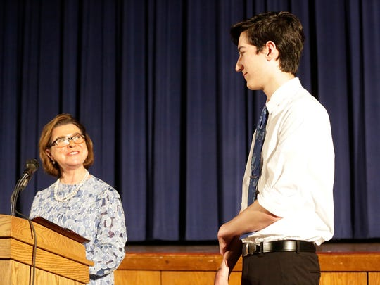 Sheboygan Falls' Benjamin Hiles smiles as he greets Natalie Black-Kohler, left, at the podium after being named the recipient of the Ruth DeYoung Kohler Scholarship during the Sheboygan Falls High School 2018 Awards and Scholarships Ceremony, Tuesday, May 23, 2018, in Sheboygan Falls, Wis.