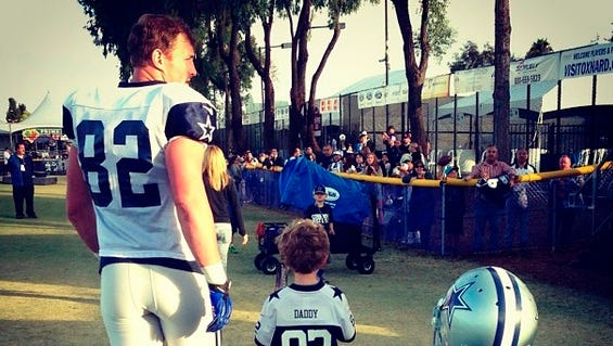 "Cowboys' Jason Witten walks with his children, who are wearing jerseys that say ""Daddy"" on the back."