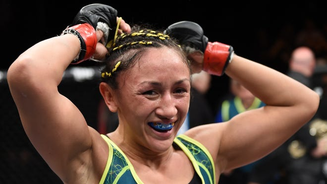 """Carla Esparza celebrates her submission victory over Rose Namajunas in their women's strawweight championship fight during """"The Ultimate Fighter"""" finale at The Palms in Las Vegas."""