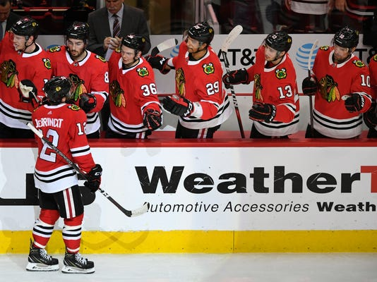 Chicago Blackhawks' Alex DeBrincat (12) celebrates with teammates on the bench after scoring a goal during the first period of an NHL hockey game against the San Jose Sharks, Monday, March 26, 2018, in Chicago. (AP Photo/Paul Beaty)
