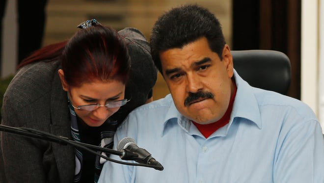 Venezuela's first lady Cilia Flores, left, speaks to her husband, President Nicolas Maduro during a demonstration, at Miraflores Presidential Palace in Caracas, Venezuela, Thursday, April 7, 2016.